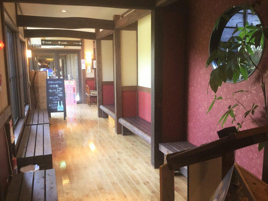 レストランから見た、玄関につながる通路。黒板の右側に占い師さんが!