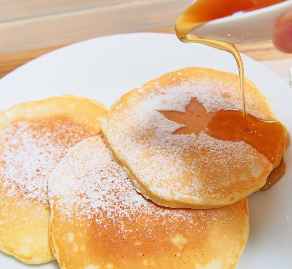 メープルベースのパンケーキにメープルシロップをかける